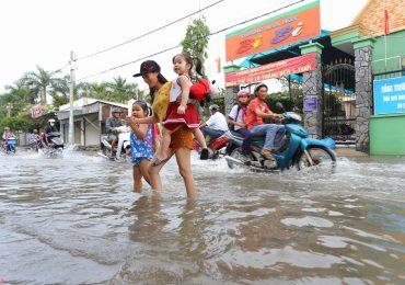 Triều cường Sài Gòn dâng cao, học sinh lội nước theo cha mẹ về nhà